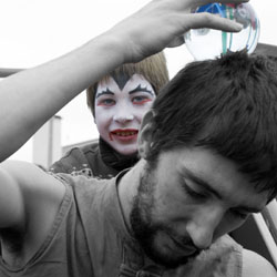 Photo of a face painted boy watching a man balance a crystal ball Photo by Andy Mason