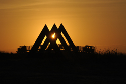 Photo showing the sunset over two sculptures in Lough Boora Parklands