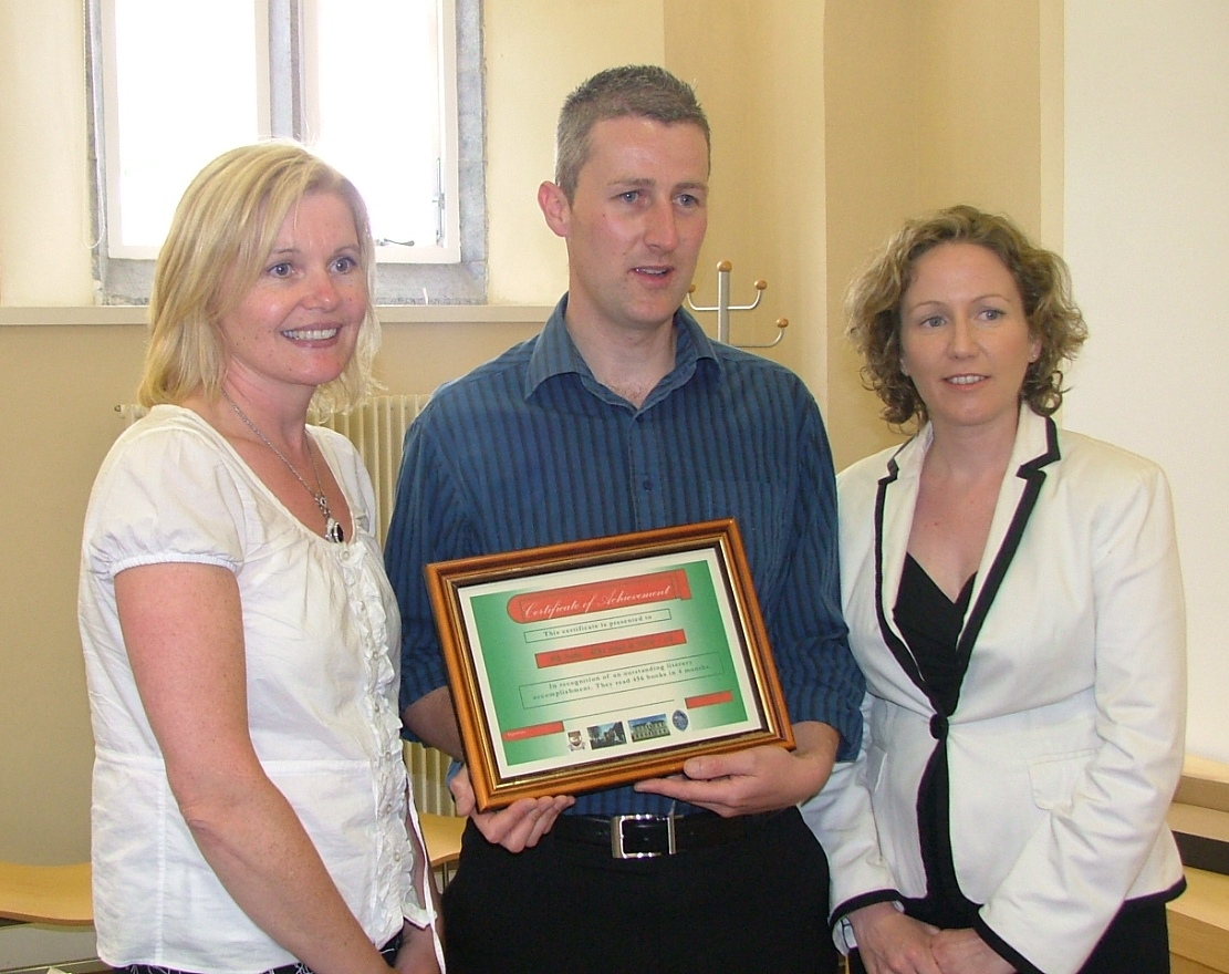 Photograph of teacher Niall Crofton receiving the certificate of achievement for the class with County Librarian Mary Stuart and Olwyn Enright, TD